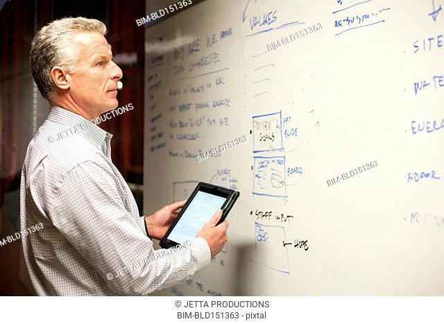 Caucasian businessman using digital tablet near whiteboard in office