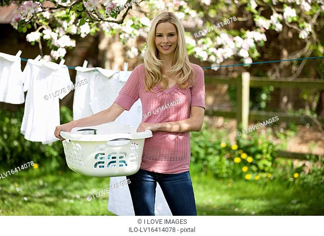A young woman holding a washing basket in front of a washing line