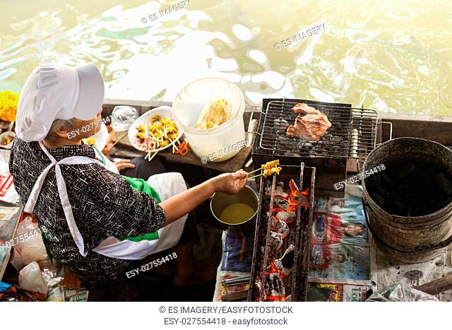 A woman in a floating kitchen prepares kebab meat in Taling Chan Floating Market, Bangkok, Thailand
