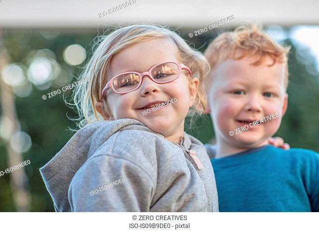 Girl and boy at preschool, portrait in garden