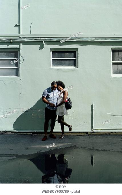 Smiling young couple standing at building at a puddle