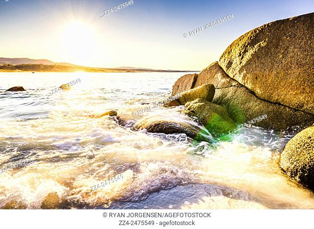 A perfect Tasmania holiday destination capturing a moving shoreline, with rocks, waves and sun light flares on a bright sunny day