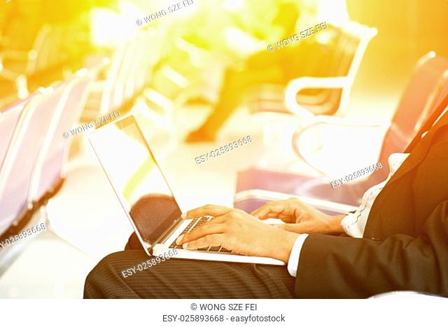 Business man using laptop while waiting his flight at airport, beautiful golden sunlight background