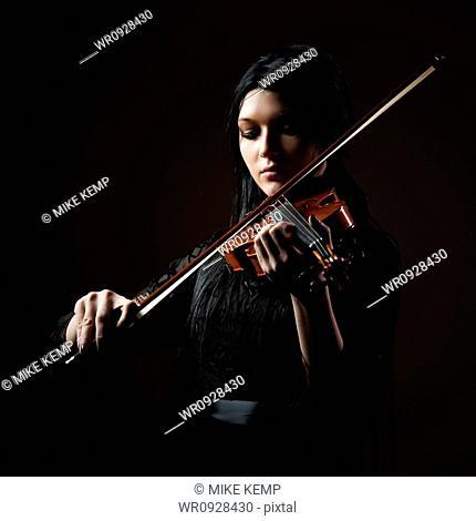 Young woman playing violin, studio shot