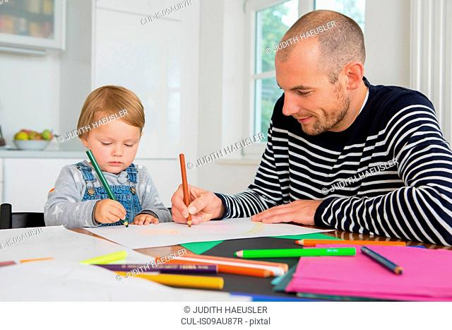 Mid adult man and toddler daughter drawing at kitchen table