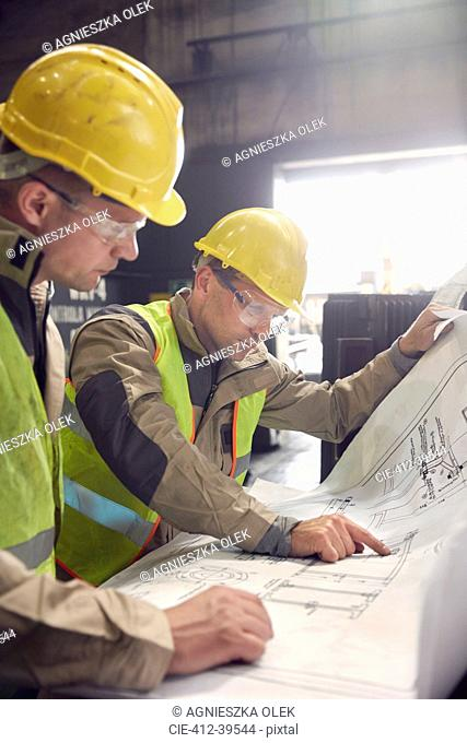 Engineer and steelworker discussing blueprints in steel mill