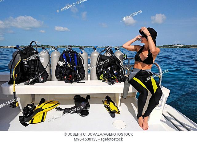 Female diver sits next to air tanks on dive boat, Bermuda Island, Atlantic