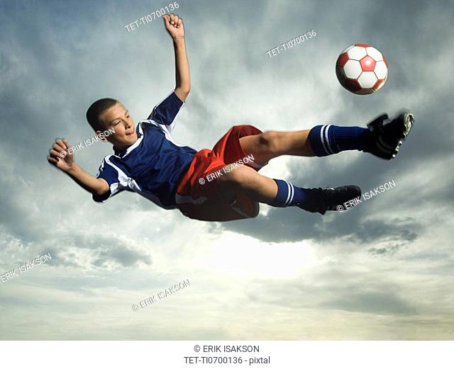 Low angle view of soccer player jumping