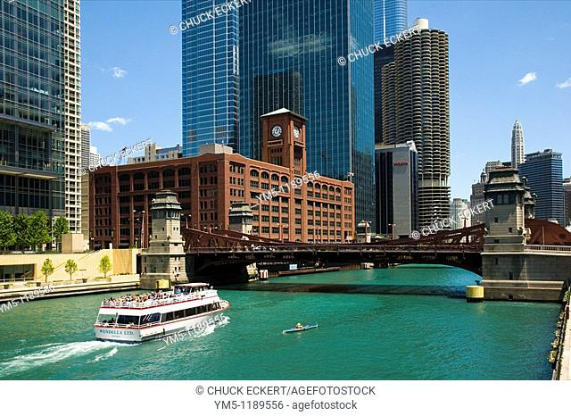 Chicago River scenic with architectural cruise boat and tiny kyaker