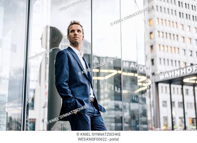 Portrait of confident businessman leaning against glass facade