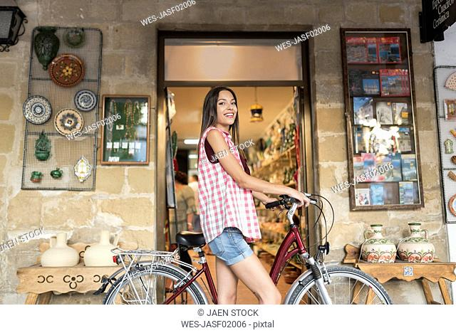 Spain, Baeza, portrait of miling young woman with bicycle in front of gift shop