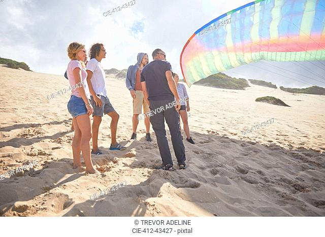 Paragliders with parachute on sunny beach