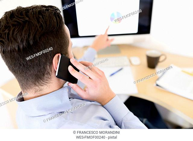 Businessman on the phone analysing pie chart on computer screen