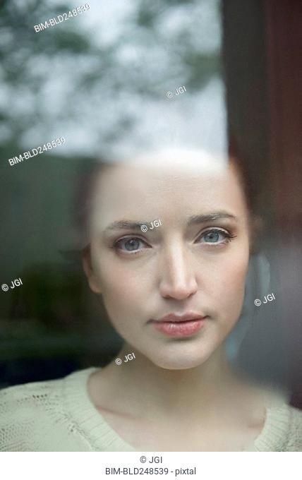 Serious Caucasian woman behind foggy window