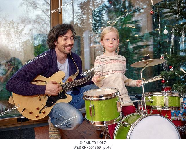 Father and daughter playing music on Christmas Eve
