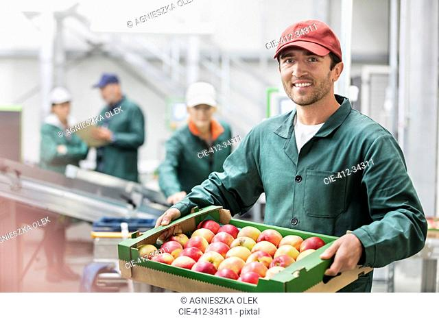 Portrait smiling worker holding box of apples in food processing plant