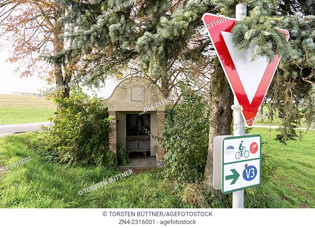 Road Sign in Front of Christian Wayside Shrine in Hausruck Region. Austria