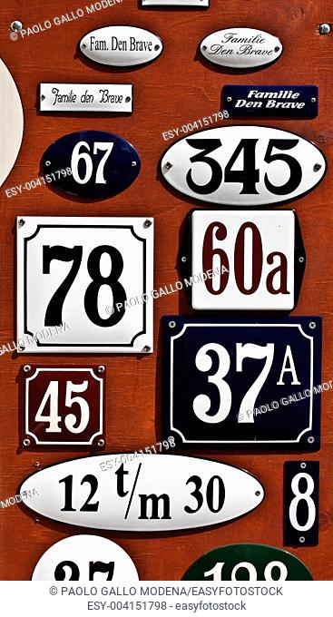 Collection of metallic plates with numbers and surnames