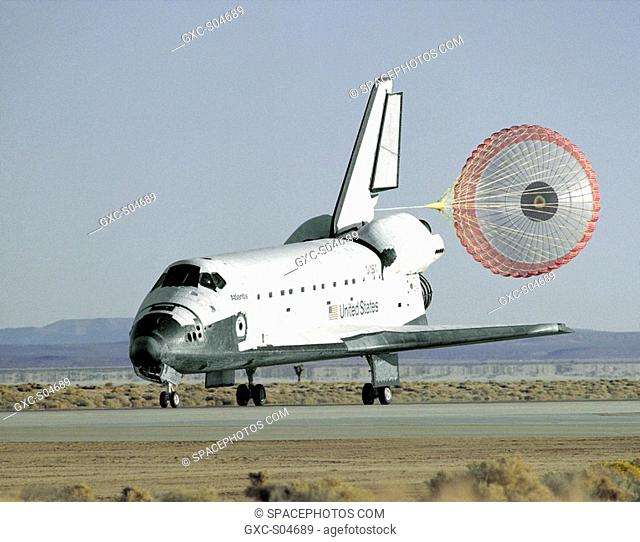 The space shuttle Atlantis lands with its drag chute deployed on runway 22 at Edwards, California, to complete the STS-66 mission dedicated to the third flight...