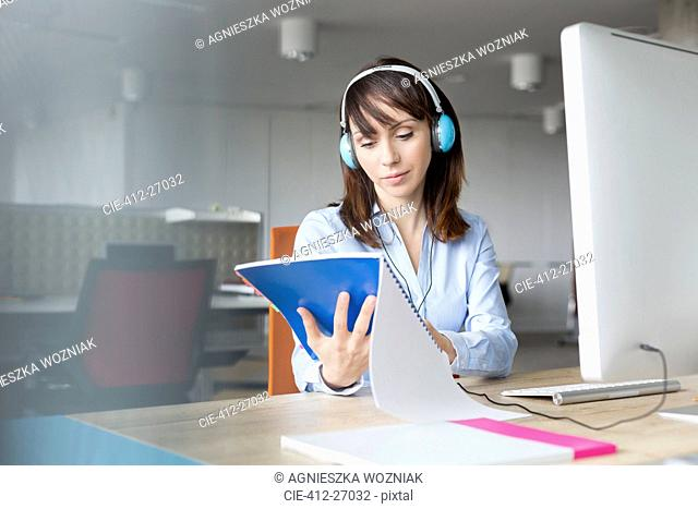 Businesswoman with headphones reading report at computer in office