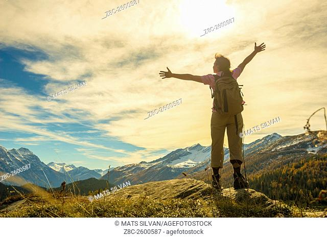 Woman with back pack and outstretched arms enjoy panoramic view over snow-capped mountain in a sunny summer day in Grisons, Switzerland