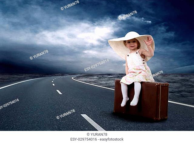 Little girl waiting on the road with her vintage baggage