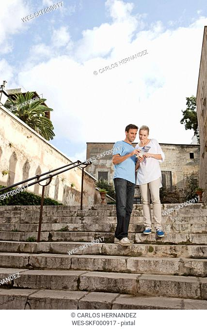 Spain, Mallorca, Palma, Couple with guidebook, smiling