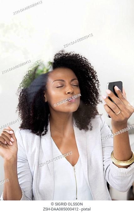 Woman blowing kiss at smartphone while doing video chat