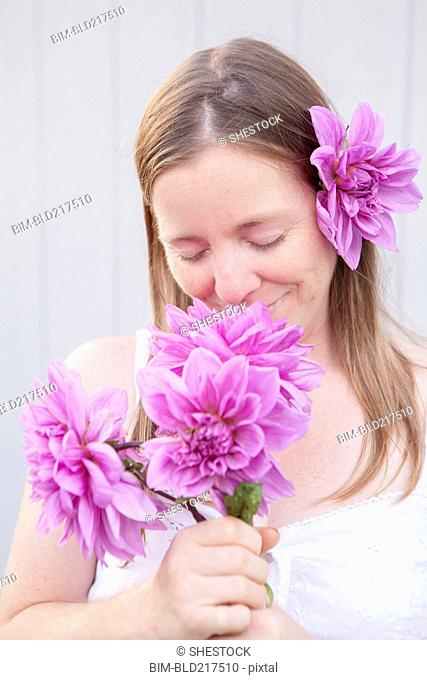Mixed race woman smelling flowers