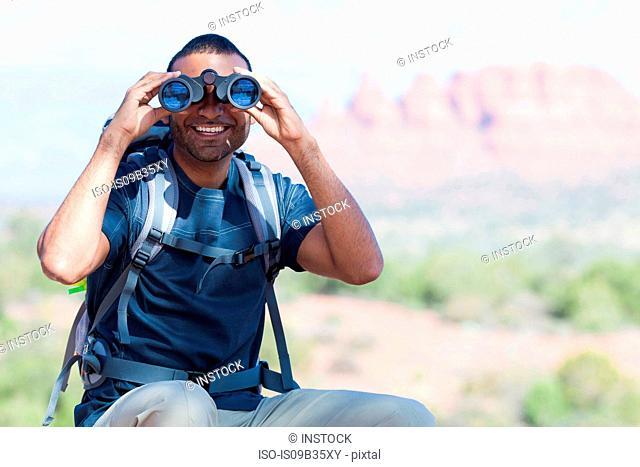 Portrait of young man looking through binoculars, Sedona, Arizona, USA