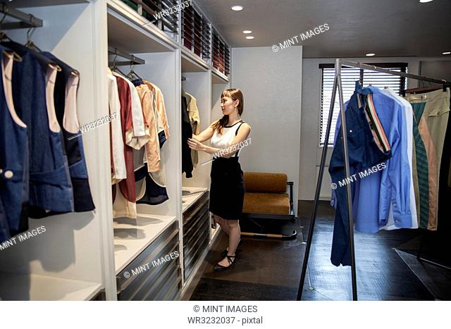 Japanese saleswoman standing in clothing store, looking at clothes rail