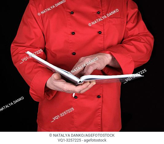 chef in red uniform holding open notepad , black background