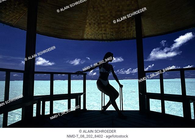 Silhouette of a woman sitting in a hut, Maldives