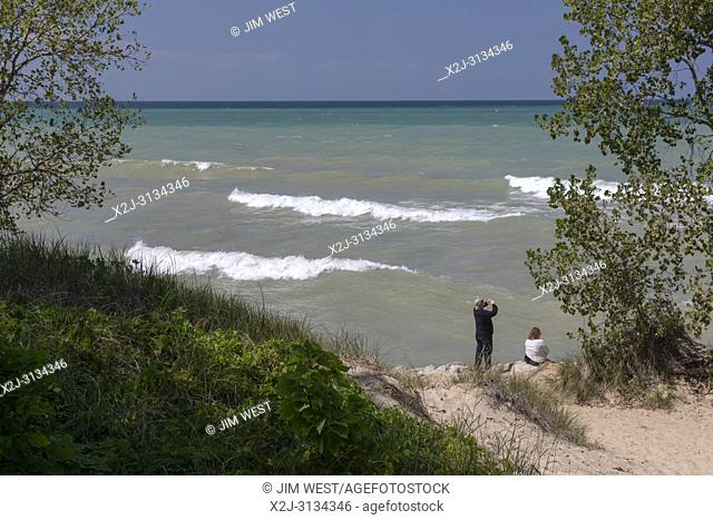 Beverly Shores, Indiana - A man and woman on the beach at Indiana Dunes National Lakeshore, at the southern end of Lake Michigan