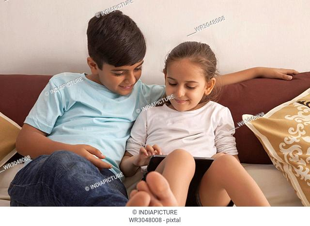 Brother and sister playing video game on digital tablet