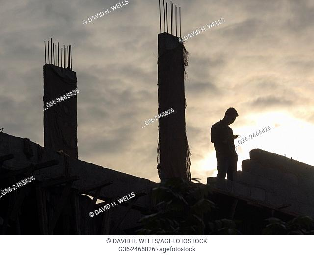 Silhouette of men working at construction site in Bangalore, Karnataka, India