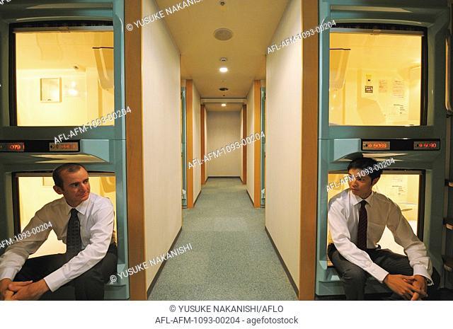 Businessman relaxing in capsule hotel