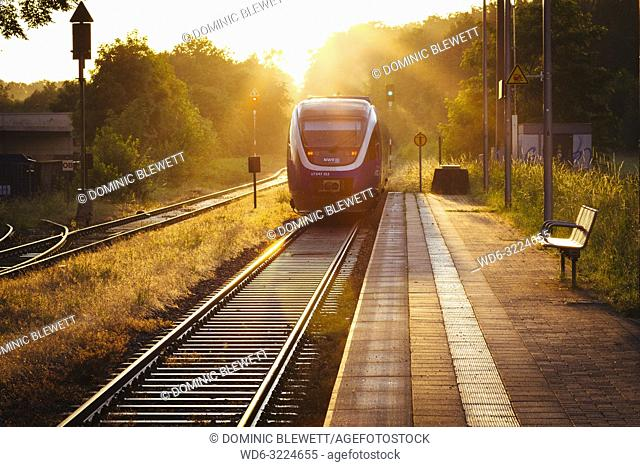 Late afternoon sunlight reflects off train tracks next to the platform as a train leaves the small train station of Quelle, near Halle (Westfalen), Germany