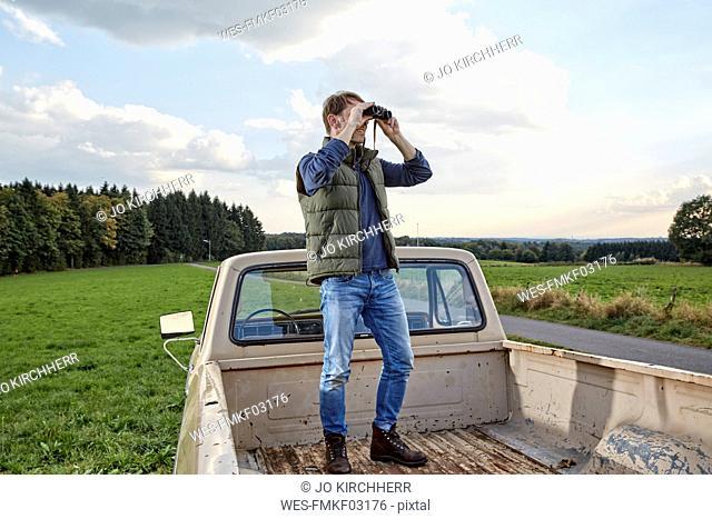 Man standing on pick up truck looking through binoculars