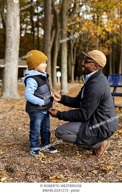 Father zipping vest for son in park