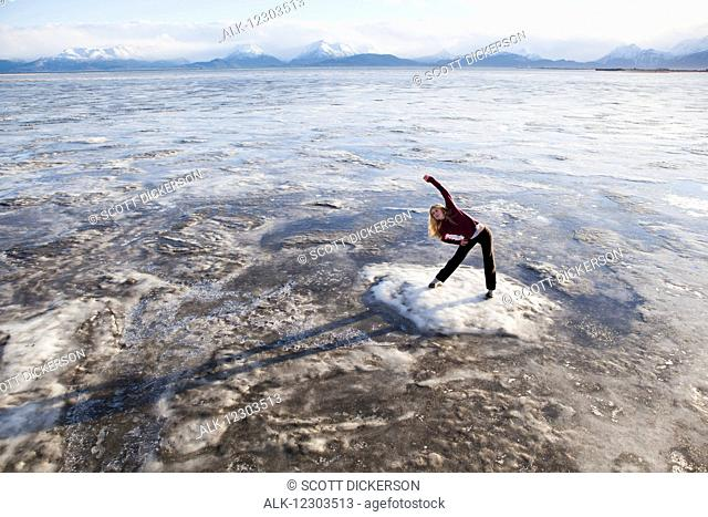 Woman stretching on an ice chunk before a run on the Homer beach, Kenai Peninsula, Southcentral Alaska