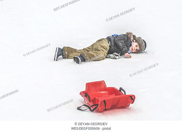 Boy lying in snow next to sledge