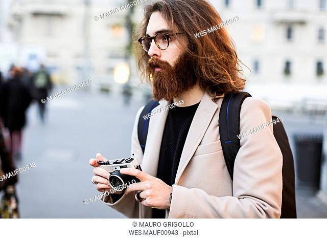 Stylish young man outdoors holding camera looking around
