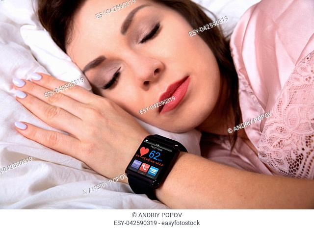 Beautiful Woman Sleeping On Bed With Smartwatch Showing Heartbeat Rate