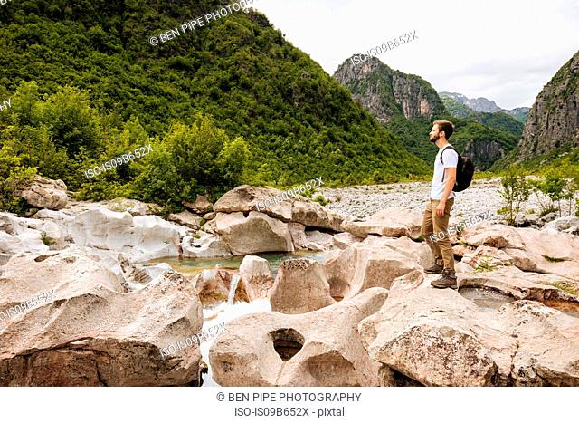 Man standing on rocks looking away, Accursed mountains, Theth, Shkoder, Albania, Europe