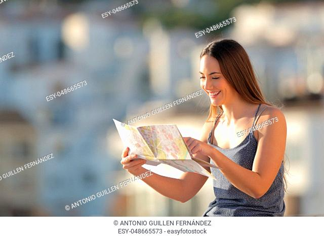Happy tourist checking paper map on vacation in a town at sunset