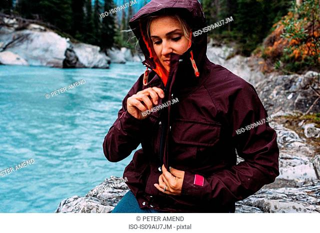 Mid adult woman by waters edge zipping up waterproof coat, Moraine lake, Banff National Park, Alberta Canada