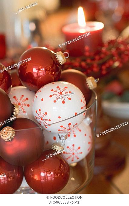 Assorted Christmas tree baubles in front of red candle