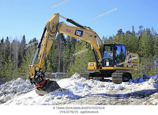 Lieto, Finland - March 22, 2019: Cat 320 hydraulic excavator on snow-topped heap of gravel at annual event of Konekaupan Villi Lansi Machinery Sales
