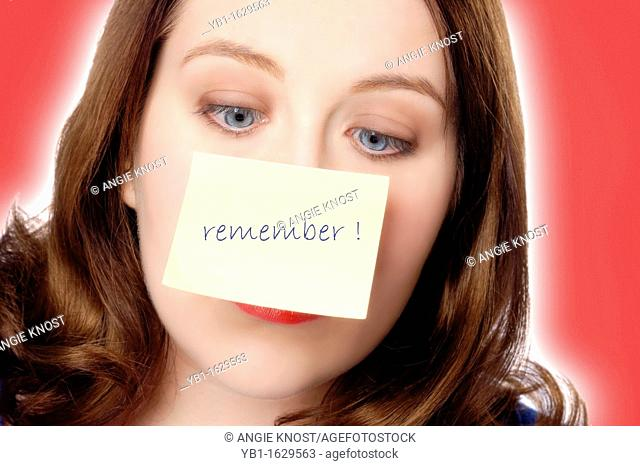 Face of an attractive woman who is looking cross eyed at a reminder note on her nose